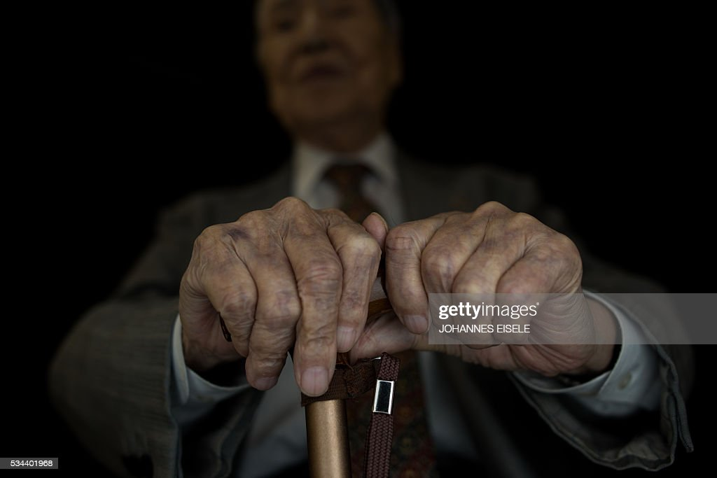 This picture taken on May 26, 2016 shows the hands of Sunao Tsuboi, a survivor of the atomic bombing of Hiroshima and a anti-nuclear and anti-war activist, as he poses for a picture at an office in Hiroshima. Tsuboi was on his way to university when the bomb exploded over Hiroshima in a flash of blinding light and intense heat on August 6, 1945. US President Barack Obama is set to become the first sitting US president to visit one of the bomb sites when he journeys on May 27, 2016 with Japanese Prime Minister Shinzo Abe to Hiroshima, hallowed ground to Japanese but, for more than 70 years, a no-go zone for 11 of his Oval Office predecessors. / AFP / JOHANNES