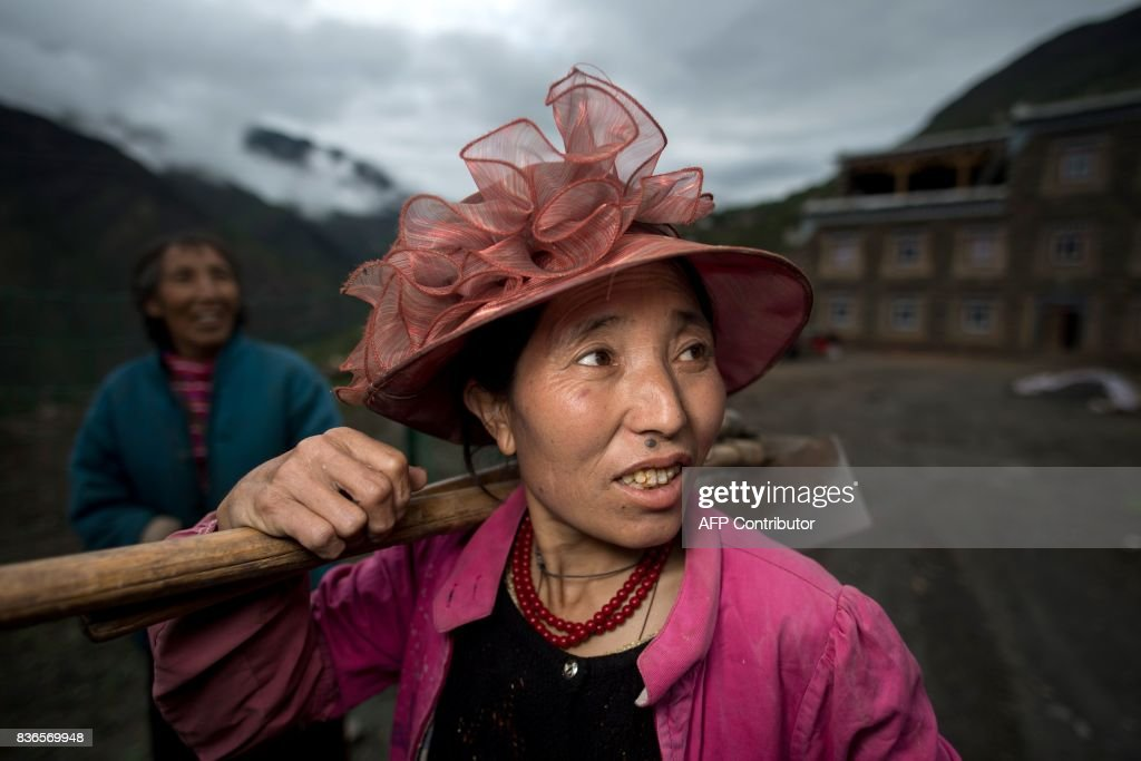 This picture taken on May 28, 2017 shows 60-year-old matriarch Dolma Lhamo (L) with one of her two daughters in front of a house in Zhaba in the valley of the Yalong River in Daofu County of the Garze Tibetan Autonomous Prefecture. The small matrilineal Zhaba ethnic group of Sichuan province eschew monogamous relationships for traditional 'walking marriages' -- so-called since men typically walk to their rendezvous before slipping through their lover's window. But the arrival of the internet, smartphones, livestreaming and popular Korean TV shows, along with improved transportation and education opportunities beyond the valley, have exposed the isolated Zhaba to other lifestyles. / AFP PHOTO / Johannes EISELE / TO