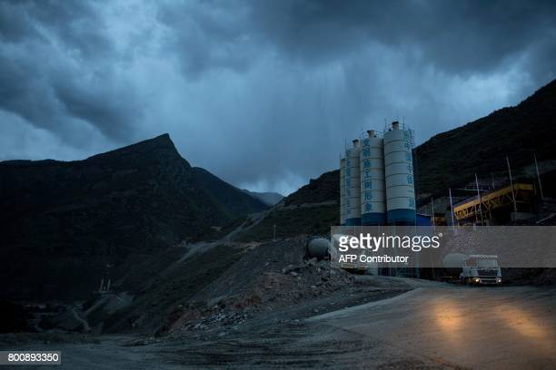 This picture taken on May 28 2017 shows a cement factory near a construction site of a bridge in a valley near Zhaba in Sichuan province Towering...