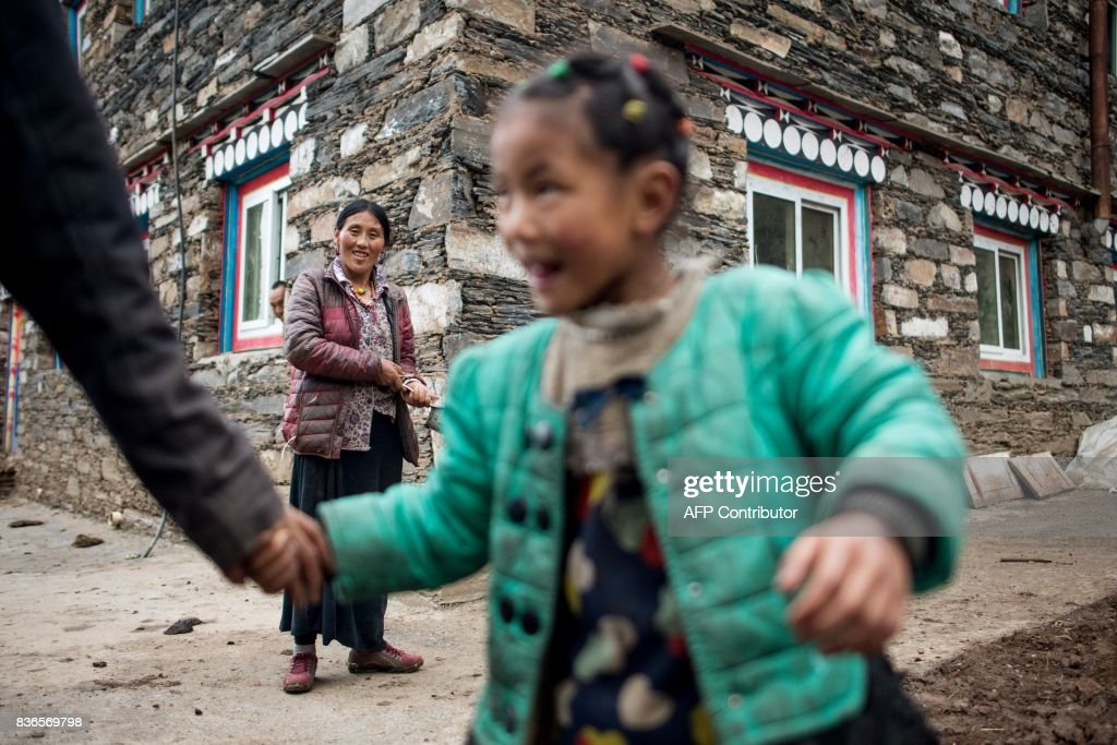 This picture taken on May 28, 2017 shows a family standing on a street in Zhaba in the valley of the Yalong River in Daofu County of the Garze Tibetan Autonomous Prefecture. The small matrilineal Zhaba ethnic group of Sichuan province eschew monogamous relationships for traditional 'walking marriages' -- so-called since men typically walk to their rendezvous before slipping through their lover's window. But the arrival of the internet, smartphones, livestreaming and popular Korean TV shows, along with improved transportation and education opportunities beyond the valley, have exposed the isolated Zhaba to other lifestyles. / AFP PHOTO / Johannes EISELE / TO