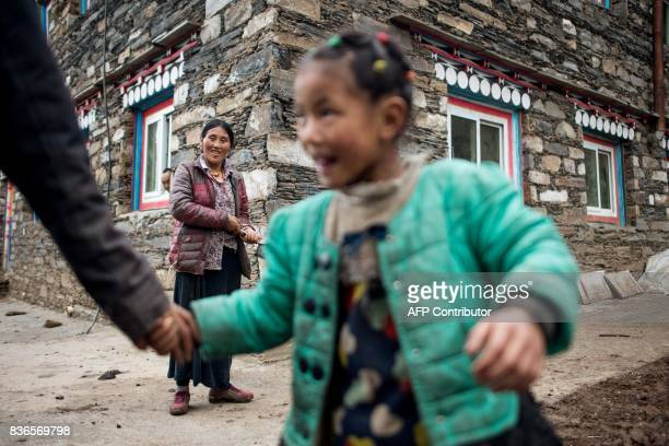 This picture taken on May 28 2017 shows a family standing on a street in Zhaba in the valley of the Yalong River in Daofu County of the Garze Tibetan...
