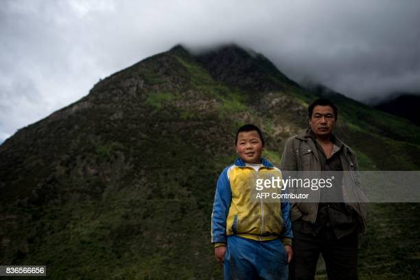 This picture taken on May 28 2017 shows a father and his son standing on a street in Zhaba in the valley of the Yalong River in Daofu County of the...
