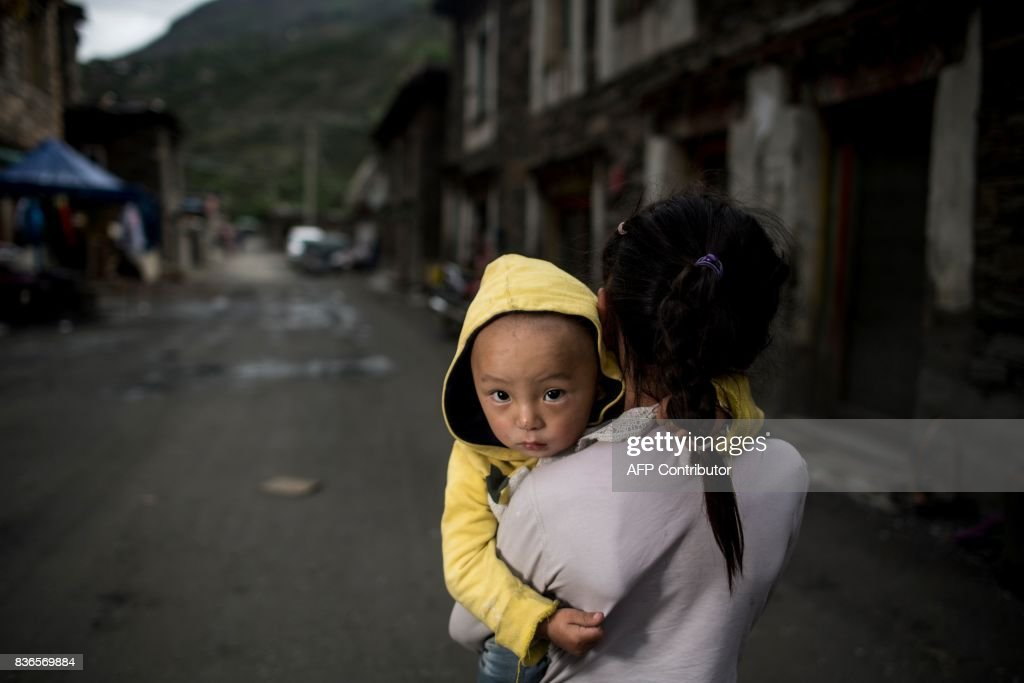 This picture taken on May 28, 2017 shows a girl carrying a boy in Zhaba in the valley of the Yalong River in Daofu County of the Garze Tibetan Autonomous Prefecture. The small matrilineal Zhaba ethnic group of Sichuan province eschew monogamous relationships for traditional 'walking marriages' -- so-called since men typically walk to their rendezvous before slipping through their lover's window. But the arrival of the internet, smartphones, livestreaming and popular Korean TV shows, along with improved transportation and education opportunities beyond the valley, have exposed the isolated Zhaba to other lifestyles. / AFP PHOTO / Johannes EISELE / TO