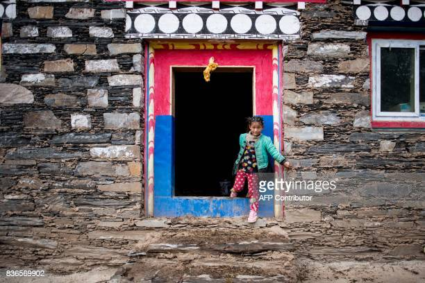 This picture taken on May 28 2017 shows a girl coming out of a building in Zhaba in the valley of the Yalong River in Daofu County of the Garze...