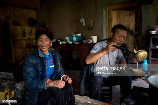 This picture taken on May 28 2017 shows a woman and a man having a breakfast consisting of yak butter tea and tsampa in their kitchen in Zhaba in the...