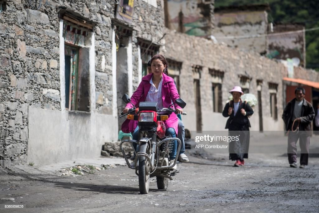 This picture taken on May 28, 2017 shows a woman riding a motorcycle on a street in Zhaba in the valley of the Yalong River in Daofu County of the Garze Tibetan Autonomous Prefecture. The small matrilineal Zhaba ethnic group of Sichuan province eschew monogamous relationships for traditional 'walking marriages' -- so-called since men typically walk to their rendezvous before slipping through their lover's window. But the arrival of the internet, smartphones, livestreaming and popular Korean TV shows, along with improved transportation and education opportunities beyond the valley, have exposed the isolated Zhaba to other lifestyles. / AFP PHOTO / Johannes EISELE / TO