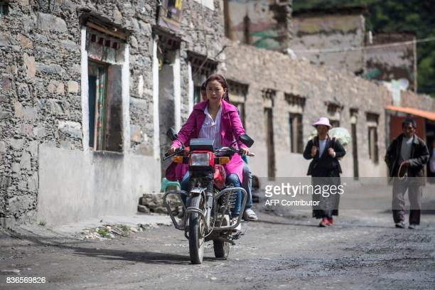 This picture taken on May 28 2017 shows a woman riding a motorcycle on a street in Zhaba in the valley of the Yalong River in Daofu County of the...