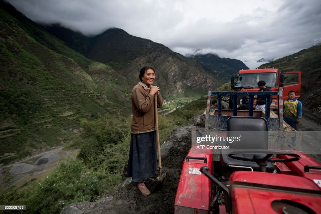 This picture taken on May 28, 2017 shows a woman smiling as she digs sand next to a street in Zhaba in the valley of the Yalong River in Daofu County of the Garze Tibetan Autonomous Prefecture. The small matrilineal Zhaba ethnic group of Sichuan province eschew monogamous relationships for traditional 'walking marriages' -- so-called since men typically walk to their rendezvous before slipping through their lover's window. But the arrival of the internet, smartphones, livestreaming and popular Korean TV shows, along with improved transportation and education opportunities beyond the valley, have exposed the isolated Zhaba to other lifestyles. / AFP PHOTO / Johannes EISELE / TO
