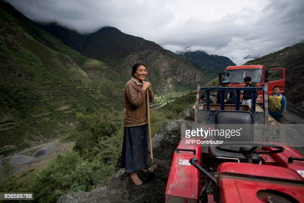 This picture taken on May 28 2017 shows a woman smiling as she digs sand next to a street in Zhaba in the valley of the Yalong River in Daofu County...