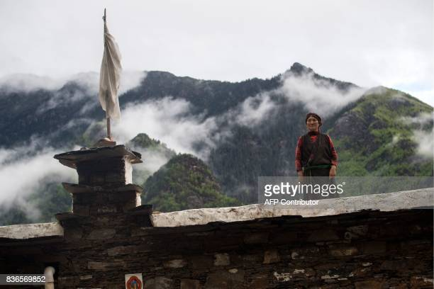 This picture taken on May 28 2017 shows a woman standing on top of a house in Zhaba in the valley of the Yalong River in Daofu County of the Garze...