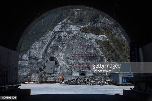 This picture taken on May 28 2017 shows a worker standing next to the construction site of the Lianghekou dam near Hekou in Sichuan province Towering...