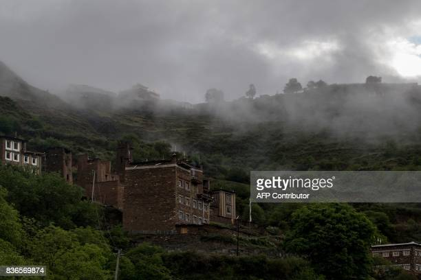 This picture taken on May 28 2017 shows fog over the houses in Zhaba in the valley of the Yalong River in Daofu County of the Garze Tibetan...