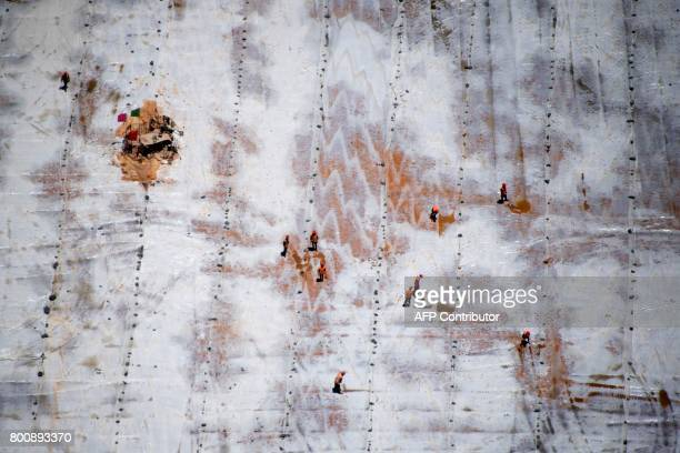 This picture taken on May 28 2017 shows workers at the bottom of the construction site of the Lianghekou dam near Hekou in Sichuan province Towering...