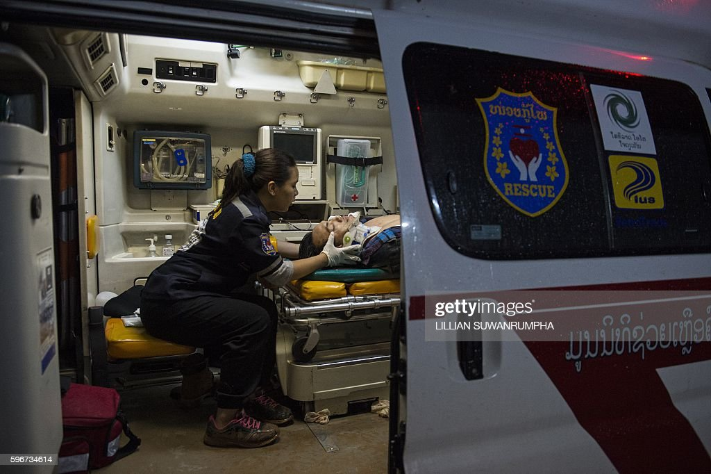 This picture taken on May 29 2016 shows a Vientiane Rescue volunteer attending to a person injured in a motorcycle accident in the back of an...