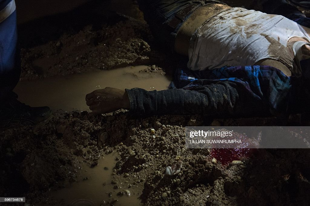 This picture taken on May 29 2016 shows an injured motorcyclist lying on an unpaved road in Vientiane Laos Founded in 2010 by a group of foreigners...