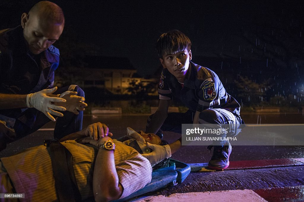 This picture taken on May 29 2016 shows Vientiane Rescue volunteer Mee Thevanth helping an injured motorcycle driver under the influence of alcohol...