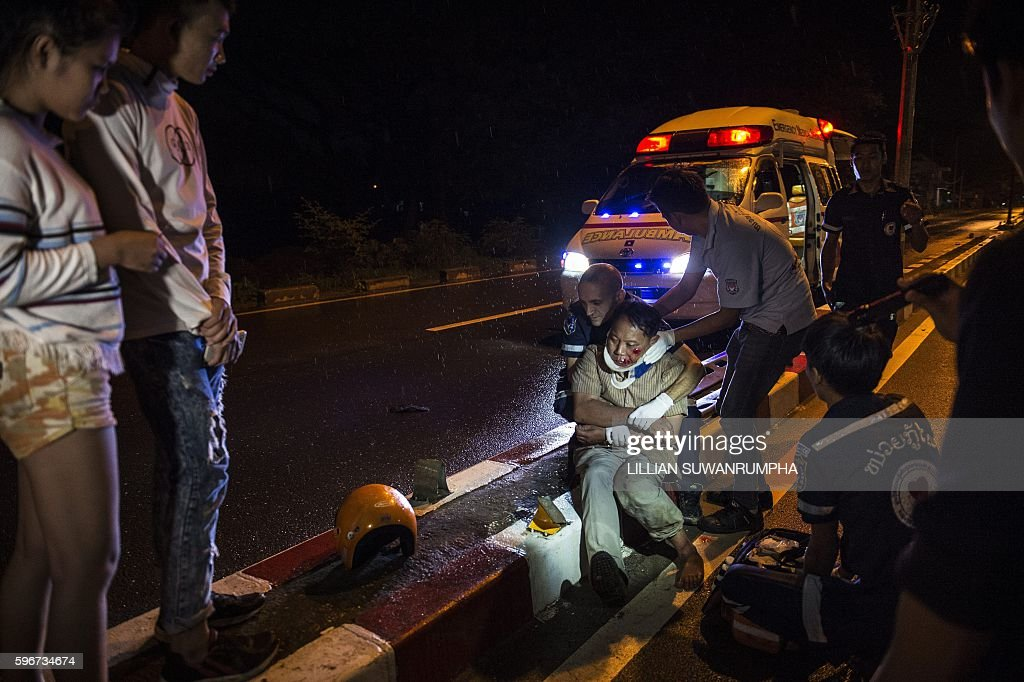 This picture taken on May 29 2016 shows Vientiane Rescue volunteers helping an injured motorcycle driver following an accident under the influence of...