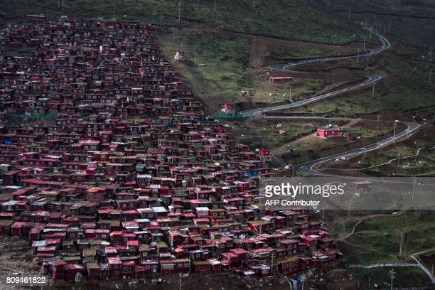 This picture taken on May 29 2017 shows the sun rising over partially demolished houses at the Larung Gar Buddhist Institute in Sertar county in...