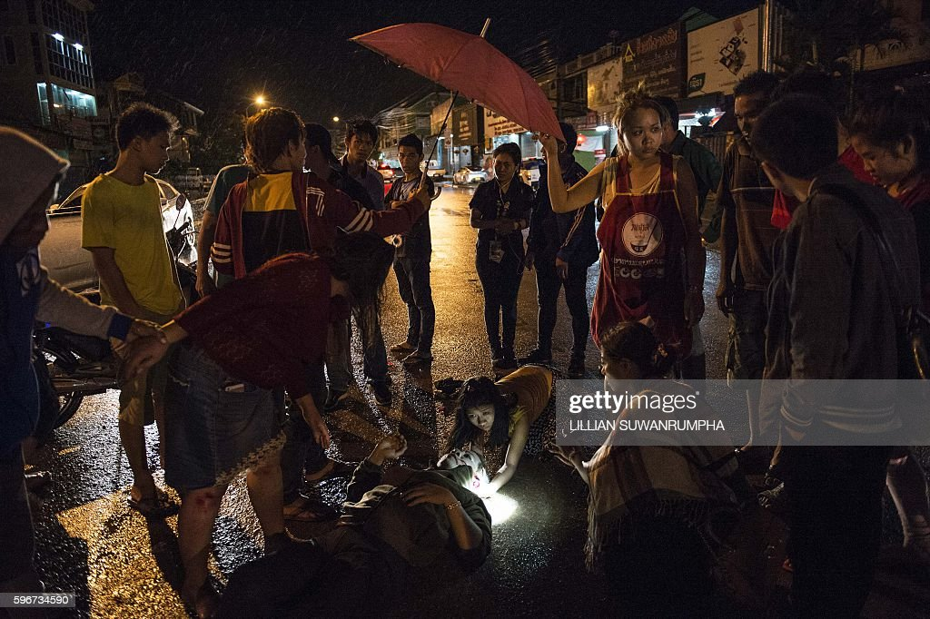 This picture taken on May 30 2016 shows people surrounding a person involved in a road accident at the scene as they wait for Vientiane Rescue...