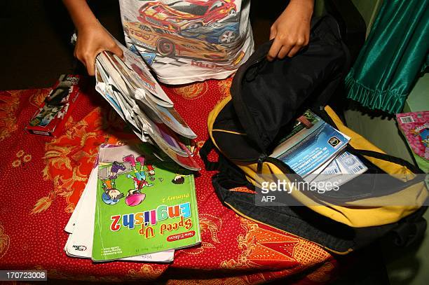 This picture taken on May 30 shows eight years old Indonesian student Wahyu packing his school bag before going to sleep at home in Rambaan vllage in...