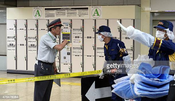 This picture taken on May 31 2015 shows police officers and a station employee putting up a Keep Out sign at a locker storage room as they inspect a...