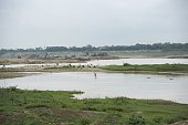 This picture taken on May 31 2016 shows a lone fisherman in front of a sand extraction site along the Mekong River in Vientiane Grain by grain...