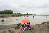 This picture taken on May 31 2016 shows families fishing near a sand extraction site along the Mekong River in Vientiane Grain by grain truckload by...