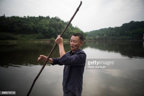This picture taken on May 31 2017 shows principal Li Congshu steering his boat as he rows students across the Xiangshuitan reservoir in Dazu district...
