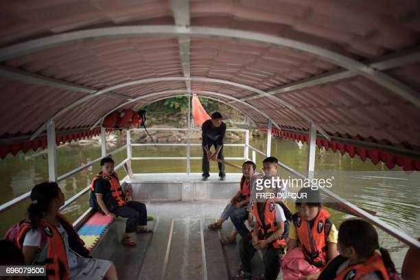 This picture taken on May 31 2017 shows principal Li Congshu steering his boat with students aboard across the Xiangshuitan reservoir in Dazu...