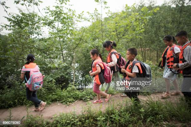 This picture taken on May 31 2017 shows students wearing lifejackets as they leave school to take principal Li Congshu's boat to cross the...