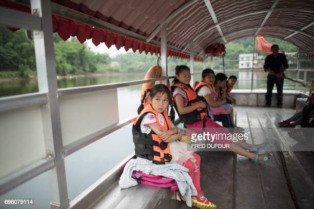 This picture taken on May 31 2017 shows students wearing lifejackets on principal Li Congshu's boat as he rows them across the Xiangshuitan reservoir...