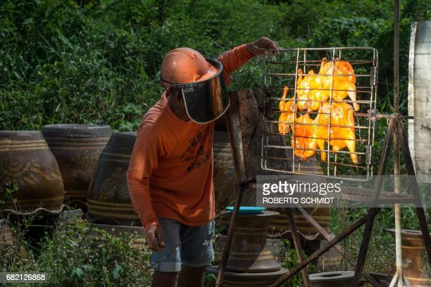 TOPSHOT This picture taken on May 4 2017 shows food vendor Sila Sutharat looking at chicken being cooked by rays of sun reflected onto an oversized...