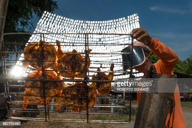 This picture taken on May 4 2017 shows food vendor Sila Sutharat turning the grates on a cart loaded with chicken as he cooks the white meat with...
