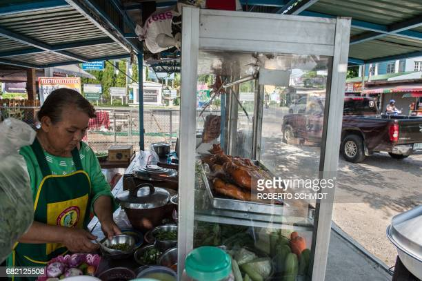 This picture taken on May 4 2017 shows Mali Pansari the wife of food vendor Sila Sutharat preparing garnishes as solarcooked chicken is displayed on...