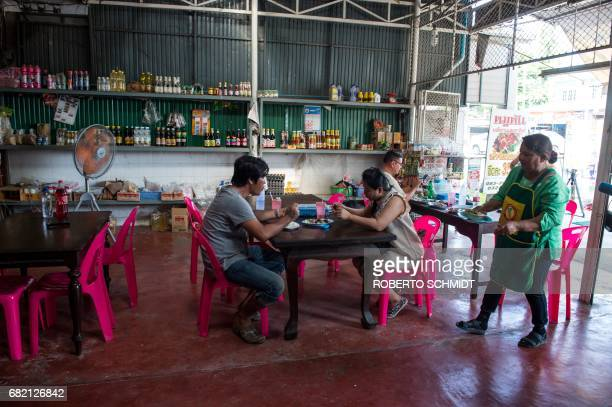 This picture taken on May 4 2017 shows Mali Pansari the wife of food vendor Sila Sutharat tending to customers in their eatery where they sell...