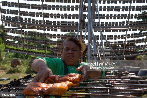 This picture taken on May 4 2017 shows Mali Pansari the wife of food vendor Sila Sutharat removing chicken from the grill after they were cooked with...