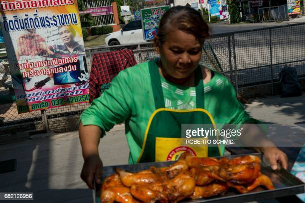 This picture taken on May 4 2017 shows Mali Pansari the wife of food vendor Sila Sutharat carrying a tray of cooked chicken past an advertising panel...
