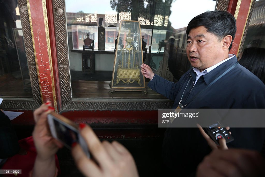 This picture taken on May 5, 2013 shows Shan Jixiang (R), president of the Palace Museum, introducing new shatterproof glass installed to protect an ancient clock the day after a similar one was damaged by a visitor, during a press conference at the Forbidden City in Beijing. A man smashed a window with his bare hands while visiting the museum on May 4, knocking the Qing Dynasty clock onto the ground and partially damaging it. The man was later taken away by the police. CHINA