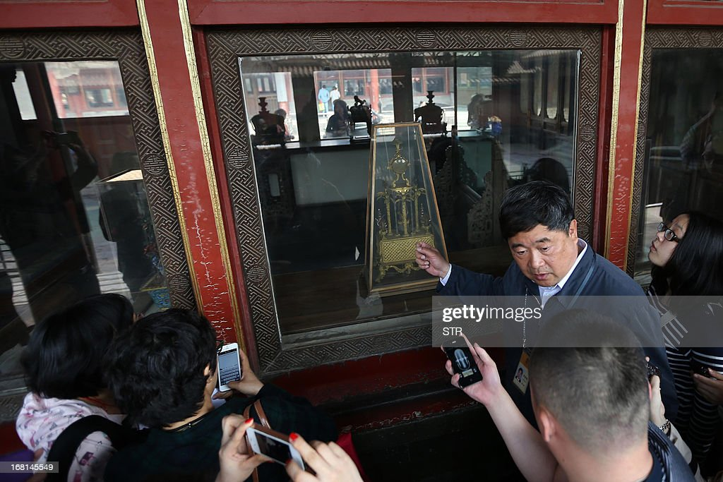 This picture taken on May 5, 2013 shows Shan Jixiang (R), president of the Palace Museum, speaking to journalists as he introduces new shatterproof glass installed to protect an ancient clock the day after a similar one was damaged by a visitor, during a press conference at the Forbidden City in Beijing. A man smashed a window with his bare hands while visiting the museum on May 4, knocking the Qing Dynasty clock onto the ground and partially damaging it. The man was later taken away by the police. CHINA