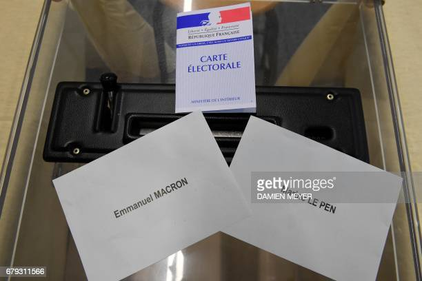 This picture taken on May 5 2017 an electoral card next to ballots for French presidential election candidate for the En Marche movement Emmanuel...