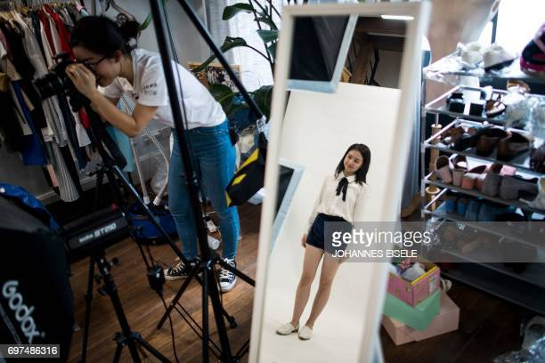This picture taken on May 5 2017 shows Wang Houhou taking pictures of a model for the website of her ecommerce startup 'gogoand' in Shanghai Hordes...