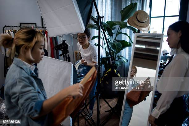 This picture taken on May 5 2017 shows Wang Ruhan and Wang Houhou taking pictures of a model for the website of their ecommerce startup 'gogoand' in...