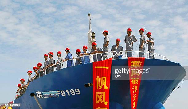 This picture taken on May 6 2013 shows staff standing on a fishing vessel setting sail for the Spratly Islands an archipelago disputed between China...