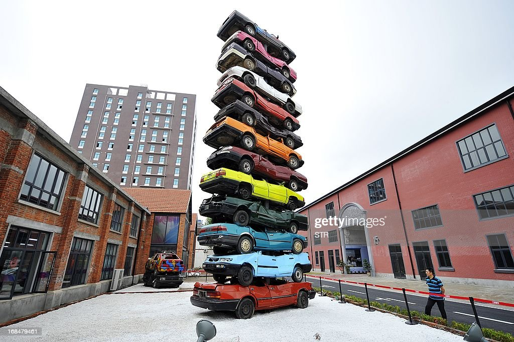 This picture taken on May 8, 2013 shows a sculpture made of 13 retired cars in 'Jiangcheng No.1' Creative Culture Park in Wuhan, central China's Hubei province. The sculpture, 'Rebirth 2013', is placed inside the park that used to be a factory back in last century. The first walking tractor of China was produced here in the factory in 1957. CHINA OUT AFP PHOTO