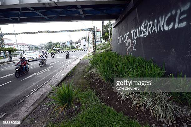 This picture taken on May 8 2016 shows motorists passing by graffiti calling for tolerance in Yogyakarta Indonesia said on August 11 2016 there was...