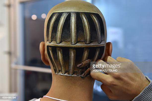 This picture taken on November 1 2014 shows a body painting of fingers sticking out from cell bars on the head of Ryonosuke Tanaka painted by...