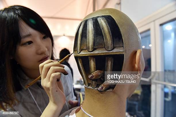 This picture taken on November 1 2014 shows Japanese bodypainting artist Hikaru Cho adding the finishing touches to a body painting of fingers...