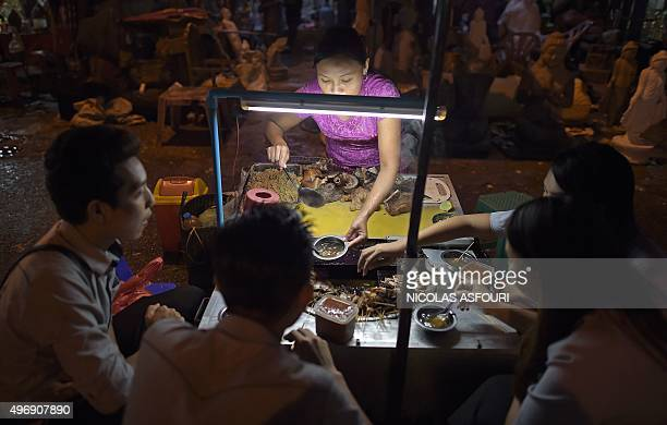 This picture taken on November 12 2015 shows people eating at a street food stall in Yangon Myanmar has been dominated by the military for half a...
