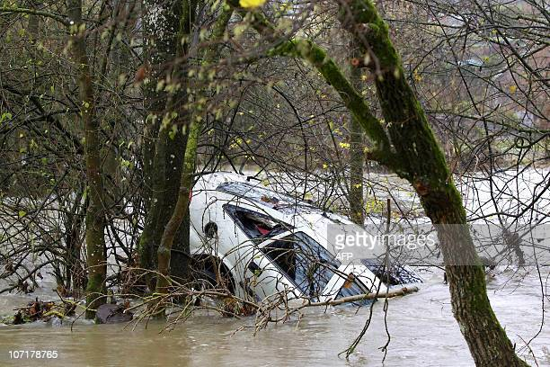 This picture taken on November 14 2010 shows a car stuck in the flooding waters in SolreSaintGery province of Hainaut A 72year old woman passenger...