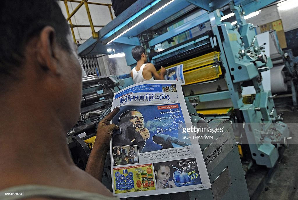 This picture taken on November 14, 2012 in Yangon shows labourers working at the printing house of a local newspaper carrying a picture of US president Barack Obama on its front-page in its latest edition. Myanmar began releasing hundreds of prisoners on November 15 under a mass amnesty that comes just days before a landmark visit by US President Barack Obama to the formerly military-ruled nation. AFP PHOTO/ Soe Than WIN